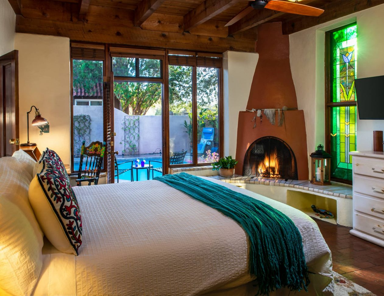 King bed in the Atanacia room at Adobe Rose Inn with a fireplace and view of the pool