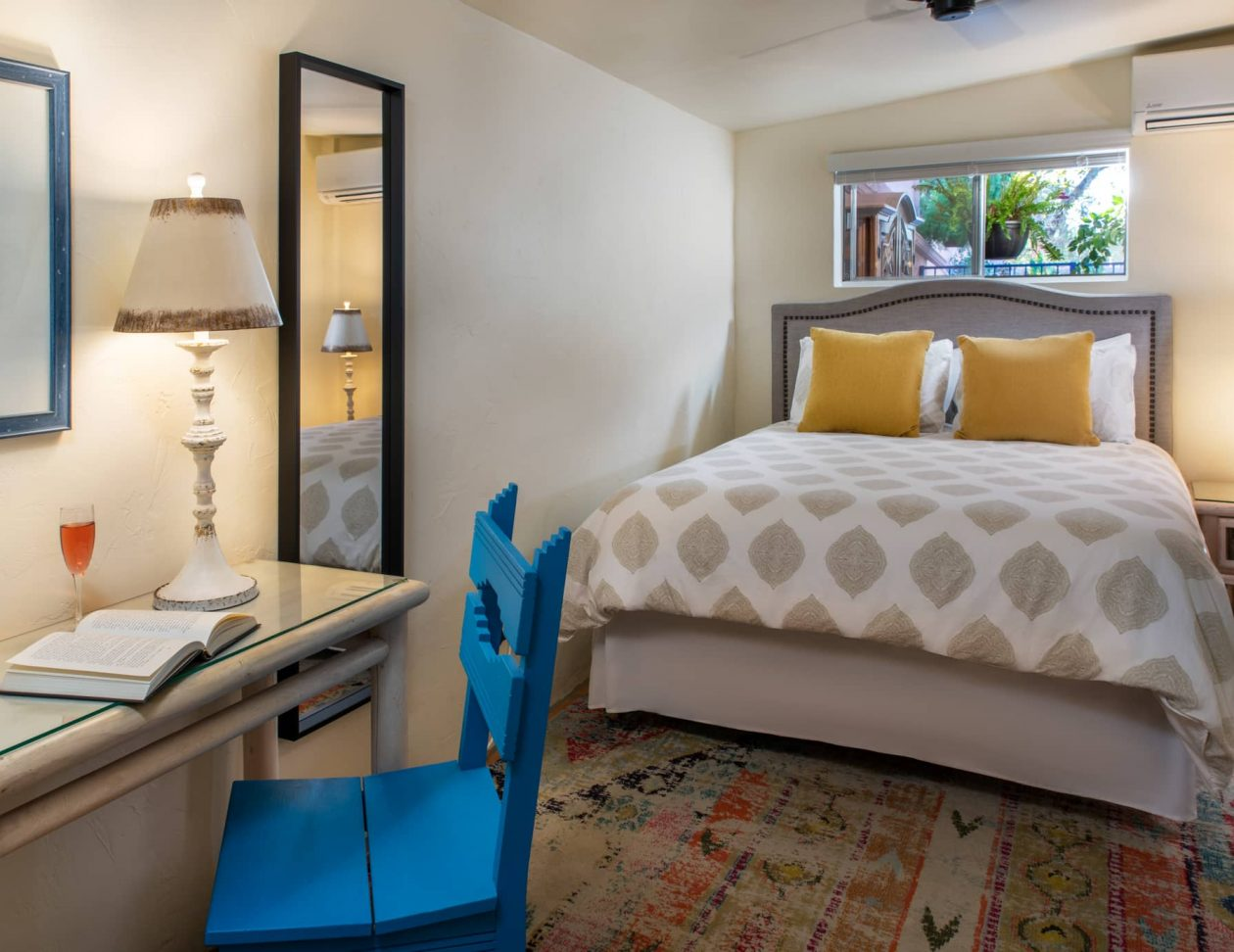 Queen bed and a writing desk in the Adobe Rose Casita