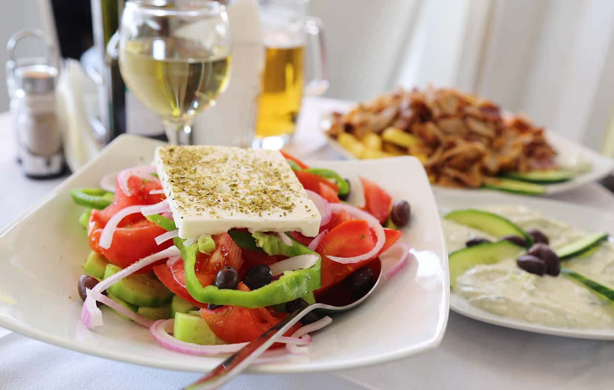 Greek salad served with a side of hummus