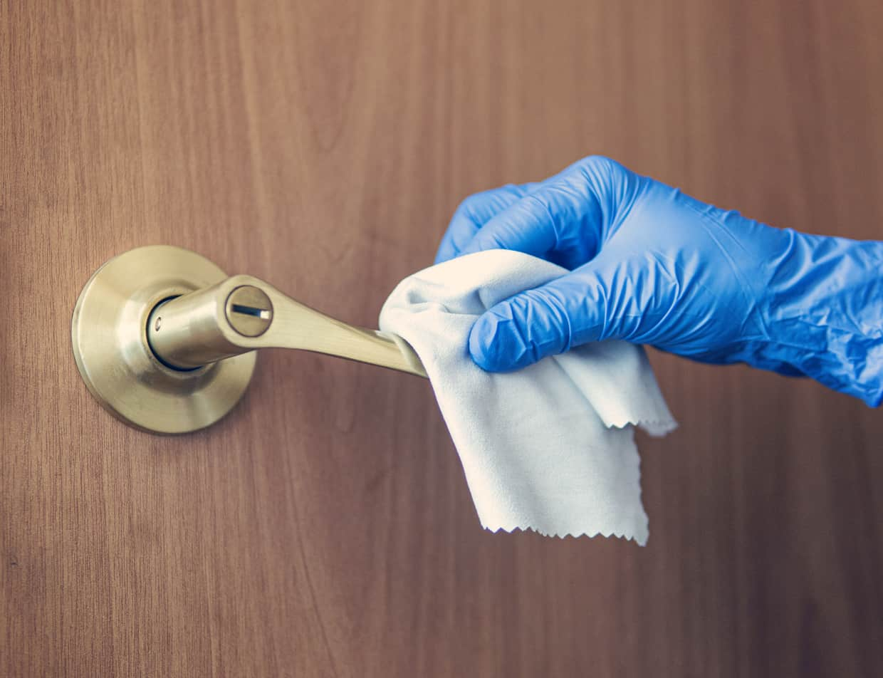 Sanitizing a door handle with gloves and alcohol